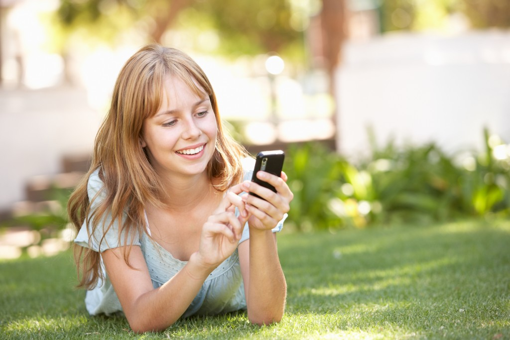 Teenage Girl Laying In Park Using Mobile Phone